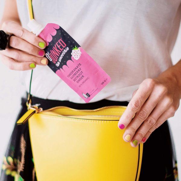 Kvinna lägger ner Dejunked chia smoothie pink i gul handväska