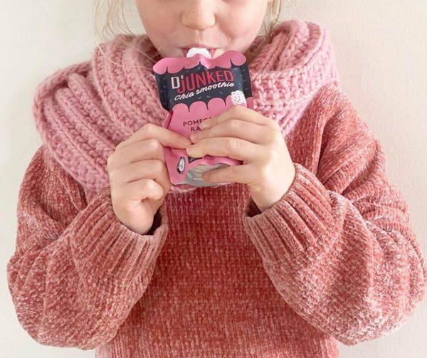 Barn i rosa tröja äter Dejunked chia smoothie pink